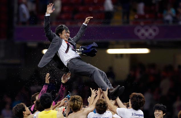 South Korea head coach Hong Myung Bo is hoisted by his players after the team won their men's football bronze medal match against Japan in Cardiff, Wales. AP