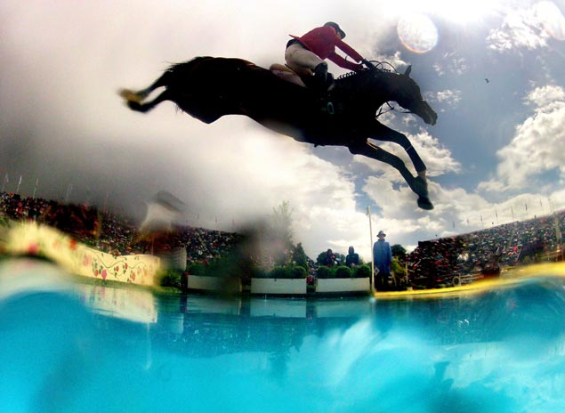 Jaime Azcarraga of Mexico and horse Gangster clear a barrier in the equestrian show jumping team competition. AP
