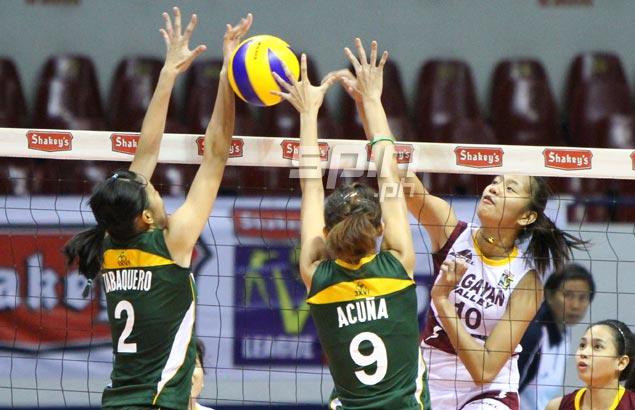 Cagayan's Sandra Delos Santos spikes past two FEU blockers. Photo by Jomar Galvez