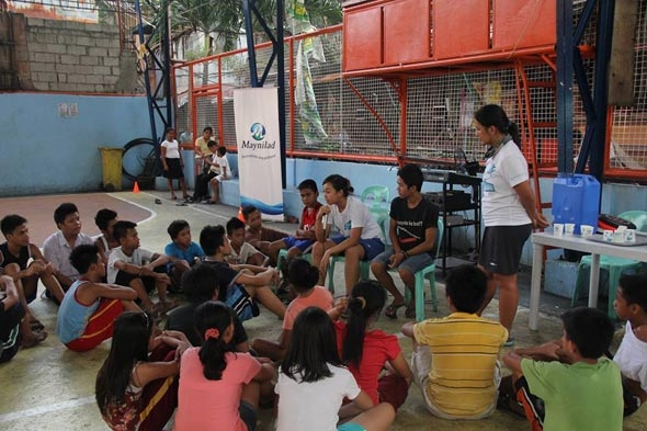 Pat Reyes (seated) talks to the kids during one of the 'Water Warriors' clinics.