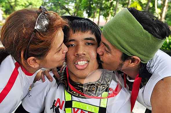 The parents of Kevin Hernandez plant him a kiss after finishing the 50K race.