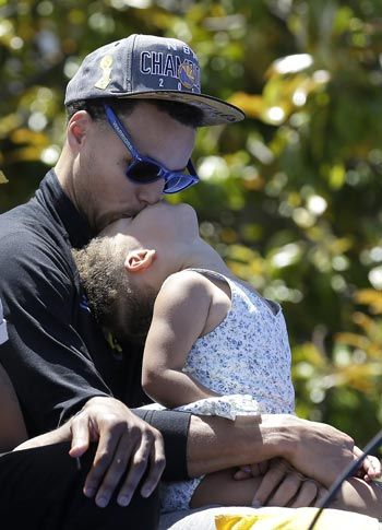 Golden State Warriors guard Stephen Curry kisses daughter Riley during the Warriors celebrations. AP