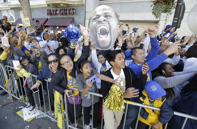 A photo of Golden State Warriors forward Draymond Green is held up by fans as they cheer. AP