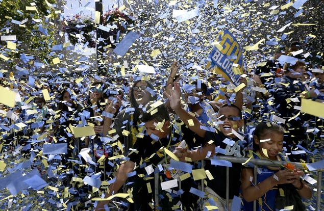 Confetti fall on fans as they cheer the Warriors during the parade and rally. AP