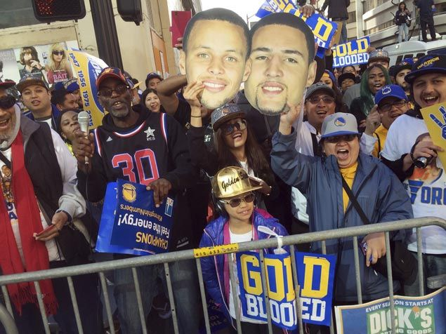 Golden State fans cheer from the sidewalk holding pictures of players Stephen Curry and Clay Thompson. AP