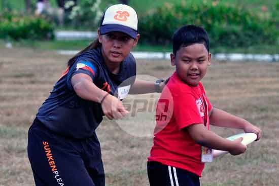 Philipppine Team and UP Sunken Pleasure player Alex Castro teaches a young student how to throw a frisbee