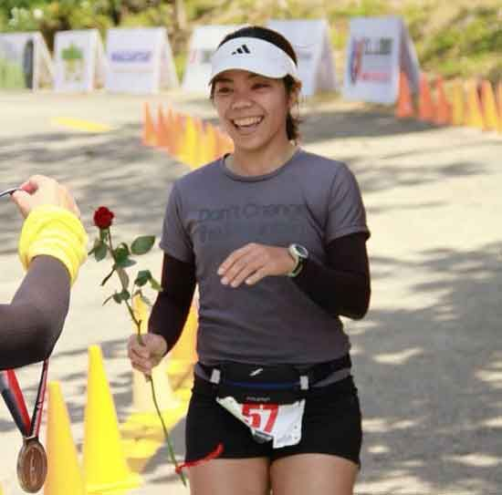 The author is all smiles as she receives her 21k medal and a rose at the finish line.