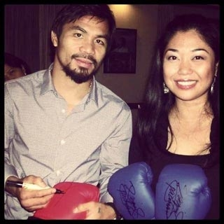 Manny Pacquiao signing the gloves for the benefit of medical missions with Janelle Pacete.