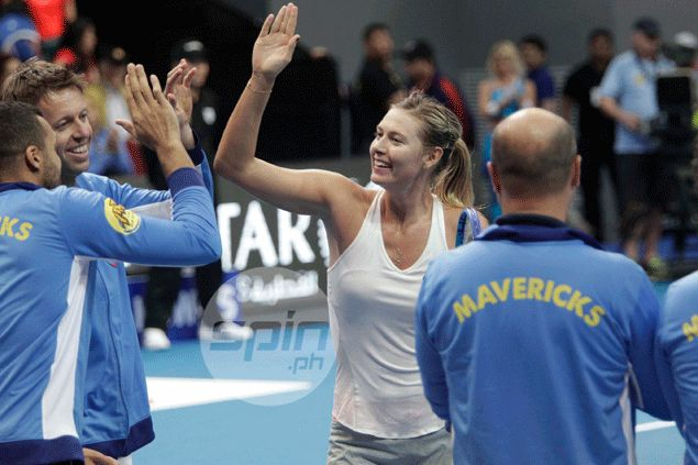 Sharapova exchanges high fives with teammates.
