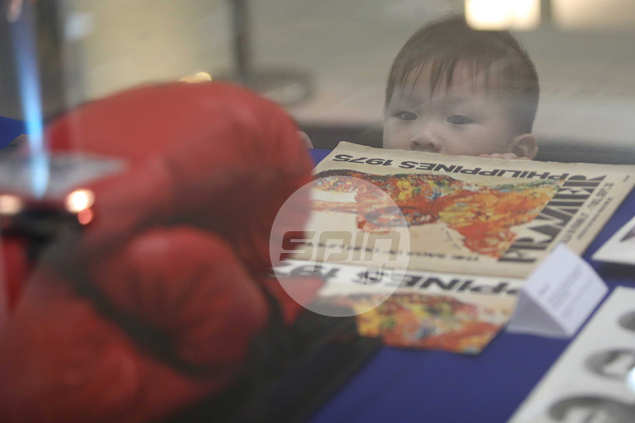 The display provides a glimpse of Ali's legendary career to an audience that includes this young boy. Jerome Ascano
