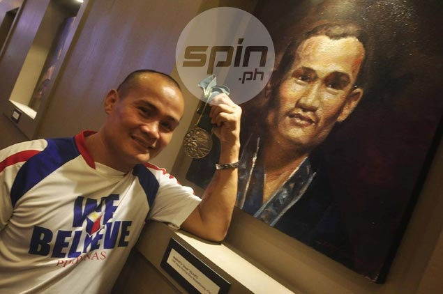 Onyok Velasco poses with his Olympic silver medal won in the 1996