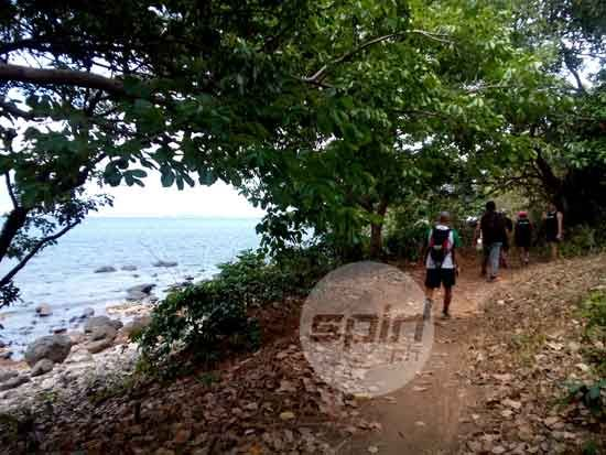 Media members check out a trail leading to the Bataan coast.