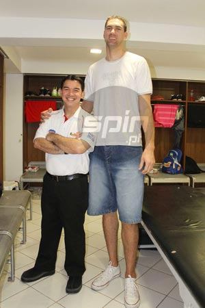 Towering import Bruno Sundov poses with Rain or Shine assistant coach Jay Legacion. Photo by Jerome Ascano