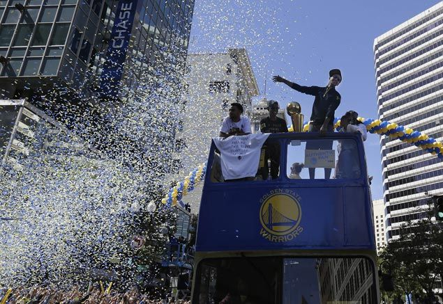 MVP Stephen Curry rides a bus during a parade and rally the NBA champions. AP