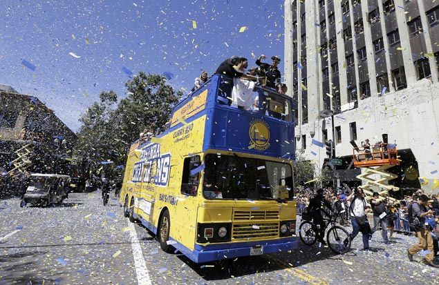 Fans celebrate as MVP guard Stephen Curry leads the victory parade. AP