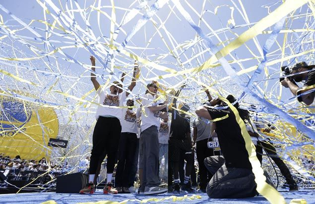 Ribbons fly as Golden State Warriors players celebrate during the victory parade. AP