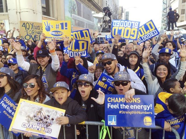 Fans cheer as the Golden State Warriors ride along during a parade and rally for winning the NBA championship. AP