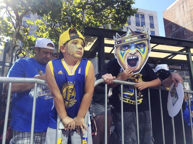 Golden State Warriors fans Vic Fontana (far left) and his son Rocco wait along the route for the NBA basketball team's world championship parade in Oakland. AP