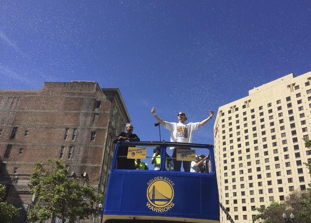 Warriors guard Klay Thompson waves as confetti fall. AP