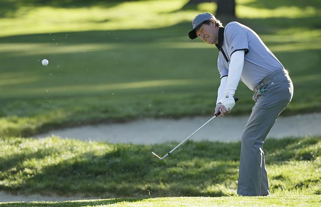 Ice hockey legend Wayne Gretzky takes a shot out of the greenside rough.