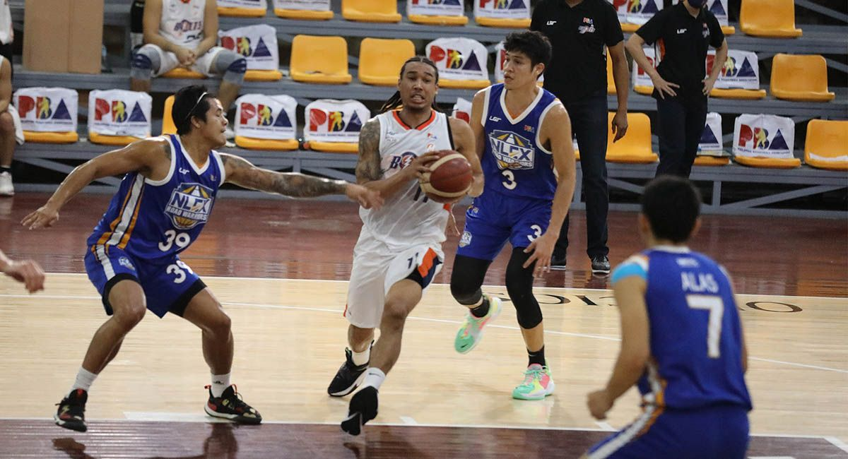 Chris Newsome of Meralco drives against NLEX defenders.