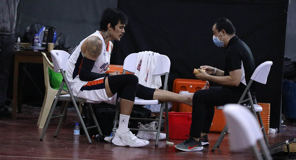 Raymond Almazan is treated for a foot injury in Game Two of the Meralco-Magnolia series.